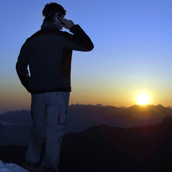 A man with mobile phone at sunrise on a mountain top, Breitenstein Mountain, Bavaria, Germany ©BELGA/imagebroker/H.Kuhbauch