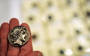 An expert from Bulgaria's National History Museum shows an ancient coin, featuring Alexander The Great. ©BELGA_AFP_N.DOYCHINOV