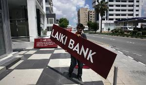 A worker takes down the sign of Laiki Bank at one of the failed bank's branches in the Cypriot capital Nicosia on May 16, 2013. Laiki or Popular Bank, the island's number two lender, was dismantled under the terms of a bailout agreed with the troika -- the International Monetary Fund, the European Commission and the European Central Bank -- in March. ©BELGA_AFP_Y.KOURTOGLOU