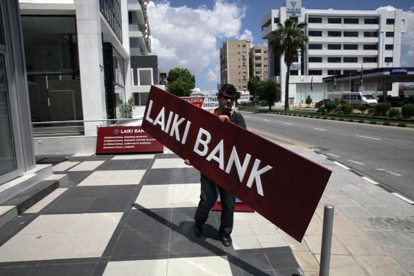 A worker takes down the sign of Laiki Bank at one of the failed bank's branches in the Cypriot capital Nicosia on May 16, 2013.