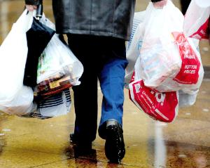 "A shopper with carrier bags as ministers have made a ""complete mess"" of moves to introduce a 5p charge on carrier bags in England"