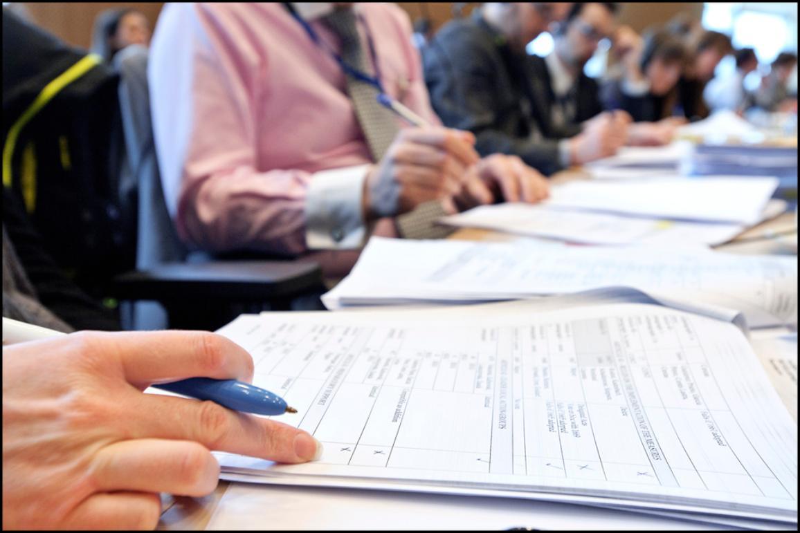 Photo des mains de députés européens travaillant sur un rapport lors d'une réunion d'une commission parlementaire