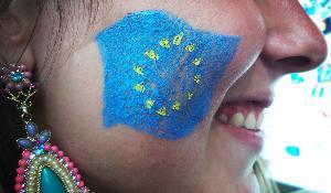 Een meisje met de EU-vlag op haar wang tijdens het EYE-evenement