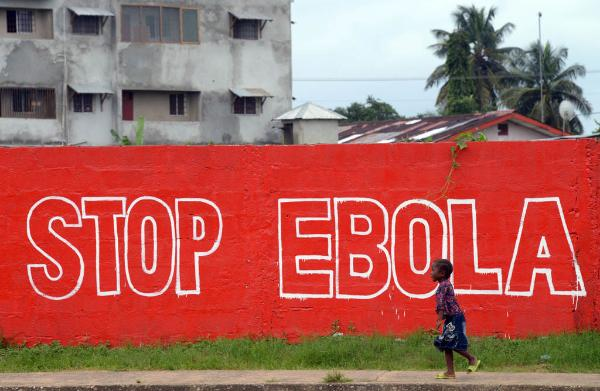 "A girl walks past a slogan painted on a wall reading ""Stop Ebola"" in Monrovia on August 31, 2014. ©BELGA_AFP_D.FAGET"
