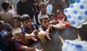 Iraqi people take water from a humanitarian aid convoy in Amerli on September 1, 2014 ©BELGA_ AFP_ JM LOPEZ