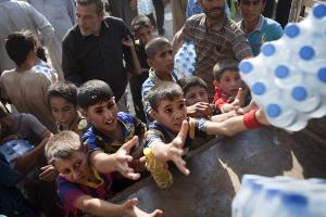 Iraqi people take water from a humanitarian aid convoy in Amerli on September 1, 2014 ©BELGA_ AFP_ JM LOPEZ