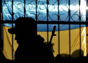 The silhouette of a Ukrainian soldier is seen against a Ukrainian flag