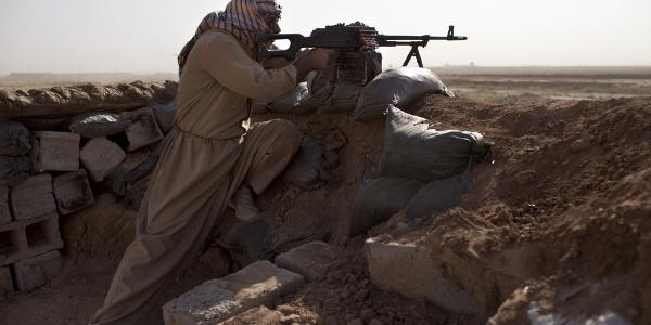 Kurdish Peshmerga fighter holds a position at a frontline where heavy clashes against Islamic States (IS) fighters take place