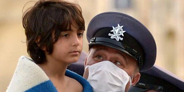 Un policía maltés con un niño rescatado tras el hundimiento de una embarcación con inmigrantes ©BELGA/AFP/M.Mirabelli.
