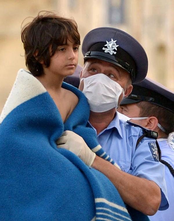 A Maltese policeman carries a child rescued by the Armed forces of Malta at Hay Wharf in Valletta on October 12, 2013. More than 140 survivors, plucked from the sea after their overloaded boat sank in the latest deadly migrant tragedy to hit the Mediterranean, arrived in Malta. The sinking killed more than 30, most of them women and children, when the boat packed with people desperate to reach European shores went down off Malta near the Italian island of Lampedusa, according to officials. ©BELGA/AFP/M.Mirabelli