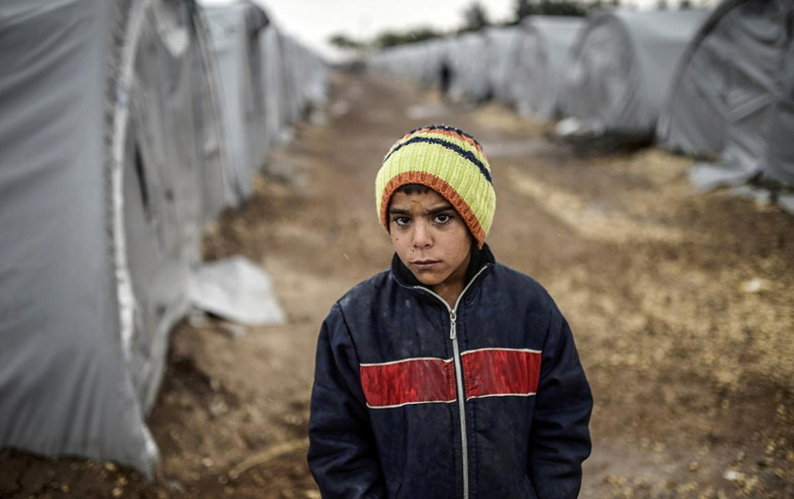 A Kurdish refugee boy stands during a rainy day at the Rojova Camp, in Suruc