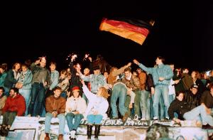 People standing on the Berlin wall, celebrating and waving a German flag. 1989. ©Belga/DPA