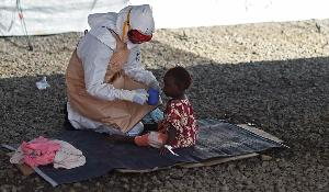 An health worker wearing protective equipment gives to drink to an Ebola young patient at Kenama treatment center run by the Red cross Society on November 15, 2014. ©BELGA_AFP_F. LEONG