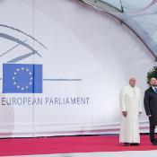 """""""La voluntad política de la gente ha de estar por encima de las presiones y los intereses de las multinacionales, cuando estos no son universales"""", declaró el Papa. (Su Santidad y el presidente Schulz escuchan el himno europeo y el del Vaticano a la entrada del Parlamento en Estrasburgo)."""