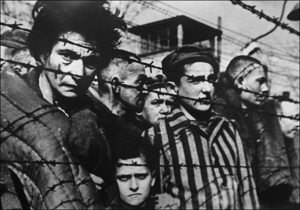 A picture of inmates behind barbed wire taken in 1945 when the concentration camp of Auschwitz was liberated in Poland