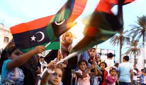Libyans wave the national flag as they gather at Martyrs' Square