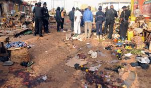 Nigerian security inspect the scene of a bomb blast at the Jos Terminus Market,Nigeria