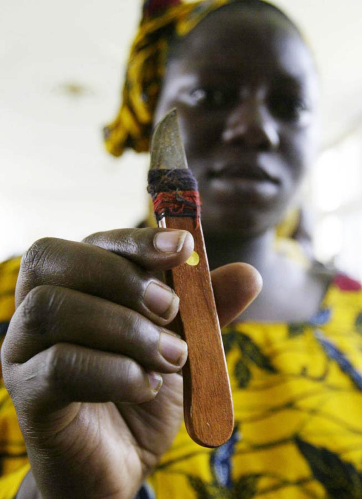A woman who performs genital cutting shows a knife she uses during a gathering to denounce excision 17 November 2005 in Abidjan. Many women in Ivory Coast undergo genital mutilation. ©BELGA_AFP/KAMBOU SIA
