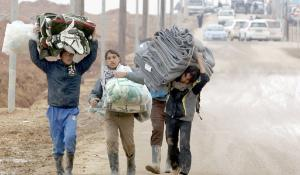 Syrian refugees carry blankets at the UN-run Zaatari refugee camp, north east of the Jordanian capital Amman
