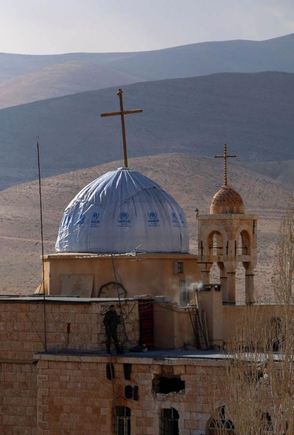 A Syrian soldier walks on the roof of the damaged church of Saint Sarkis, in the ancient Christian town of Maalula, 56 kilometers northeast of the Syrian capital Damascus, on December 20, 2014. ©BELGA/AFP/Y.Karwashan