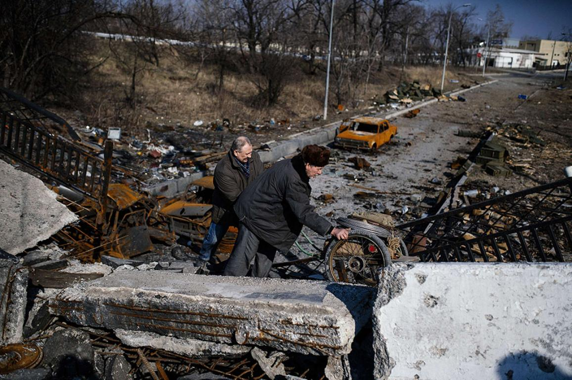 Men push a cart over the destroyed Putilovka bridge near Donetsk airport on March 21, 2015.