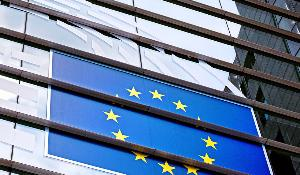 Parliament building in Brussels. Photo of glass wall with large EU flag