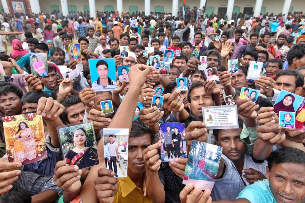 Relatives of Rana Plaza victims hold photos of their loved ones. A year ago this week, more than 1,100 factory workers died when the eight-story Rana Plaza building in Dhaka, Bangladesh collapsed into a heap of bricks and fabric bolts. @Rohat Ali Rajib
