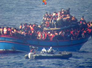 Refugees on a boat on the Mediterranean Sea between North Africa and Sicily who are being rescued by the Italian Navy