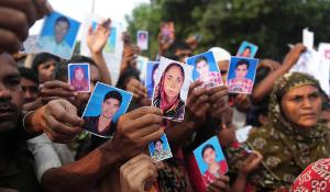 In this photograph taken on April 27, 2013 Bangladeshi relatives hold photos of the missing and dead workers three days after an eight-storey building collapsed in Savar, on the outskirts of Dhaka.  ©BELGA_AFP_Munir Uz Zaman