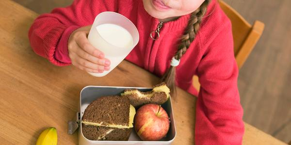 Child drinking milk and eating healthy food