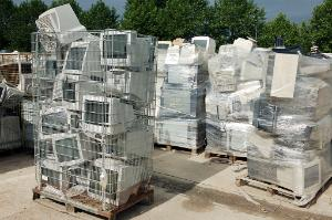 Computer equipment recycling centre. Cages and pallets of old computer monitors waiting to be recycled at a recycling centre.