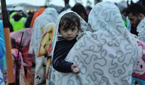 Syrian refugee child in her mother's arms waiting in the rain for permission to move into a yard to take buses for their onward journey into Austria. ©UNHCR/Mark Henley