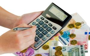 Euro coins and banknotes, a person holding a calculator and a pen