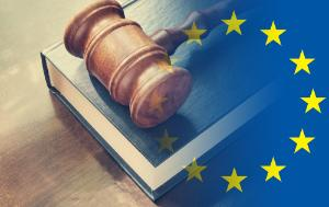 Wooden gavel on top of book on a wooden table. European flag illustration.
