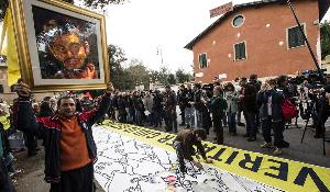 A man holds up a portrait of Giulio Regeni, the Italian student slained in Cairo, as several dozen people stage a sit-in outside Egypt's embassy in Rome. ©Massimo Percossi/AP Photos/European Union-EP