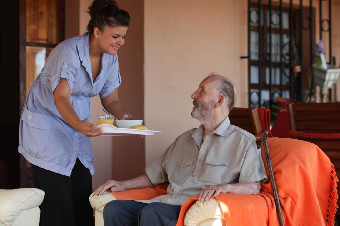 A nurse giving food to a senior man ©AP Images/ European Union-EP