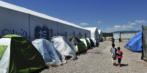 Две деца бежанци сред палатки в лагера Идомени, Гърция