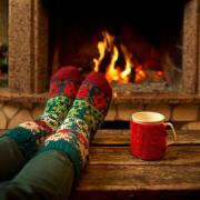 Feet in woollen socks by the fireplace with a cup of hot drink