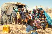 Photo showing a mother of five children and other internally displaced Somalis in front of a make-shift tent