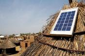 small solar panel on straw thatched hut in Rwanda