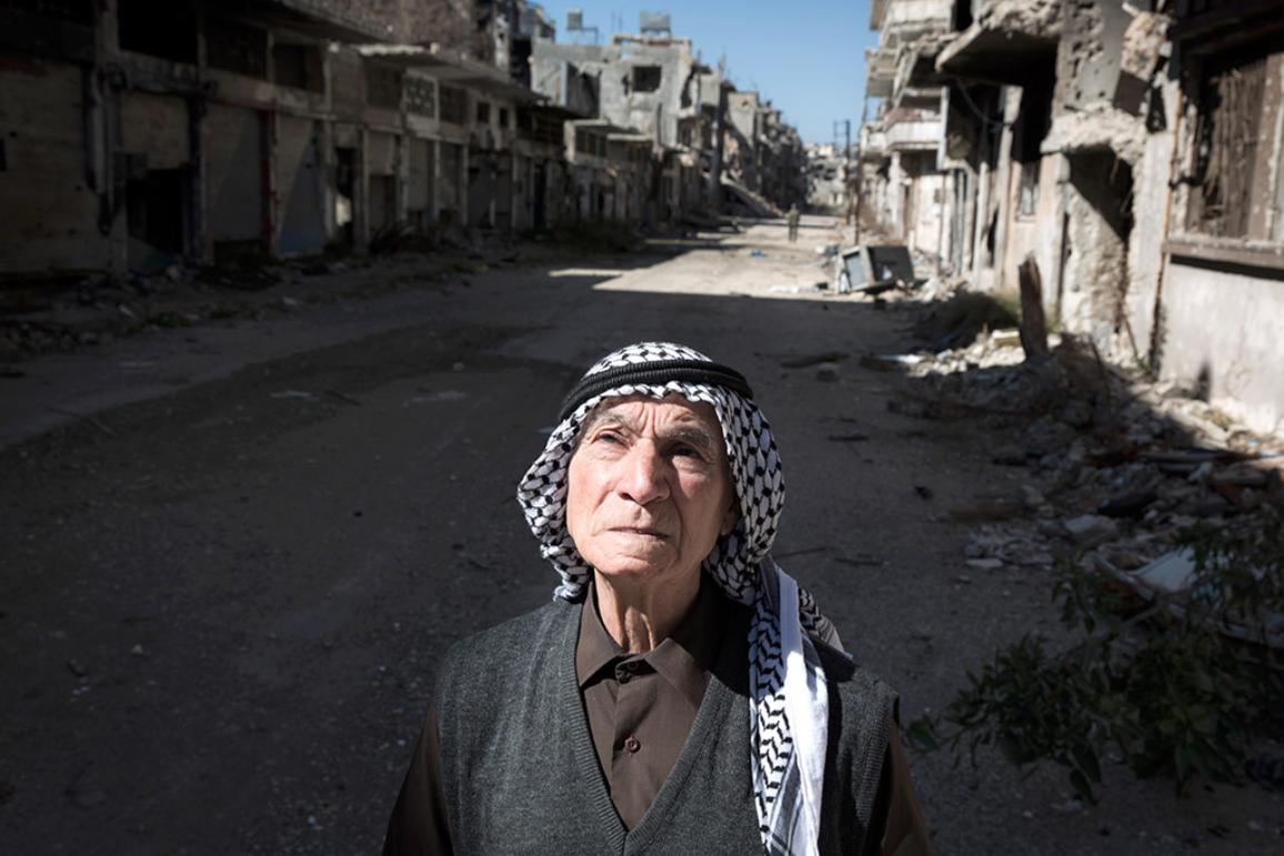 Foto: imagen de una anciana en una calle de Homs, Siria, llena de escombros