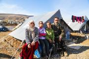 Syrian family sitting in front of a tent in a refugee camp