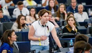 Photographie d'une jeune femme prenant la parole en plénière lors du EYE2016
