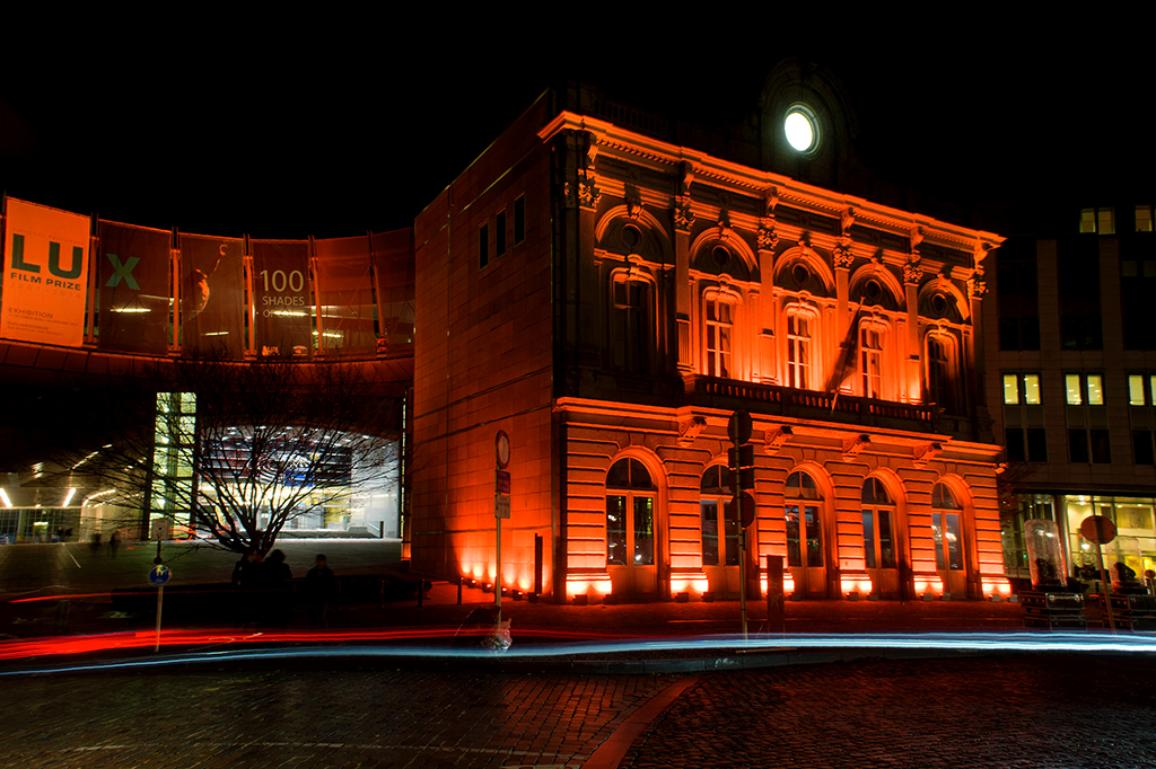 Nighttime photo of a Parliament builiding in Brussels lit orange to mark the International Day for the Elimination of Violence against Women