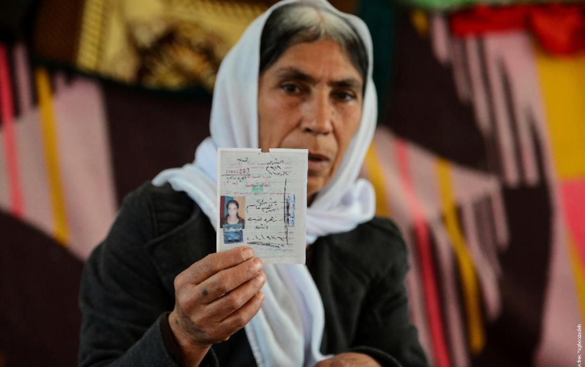 1/5 An older Yazidi woman in headscarf shows her missing daughter's Iraqi ID card  ©Alfred Yaghobzadeh