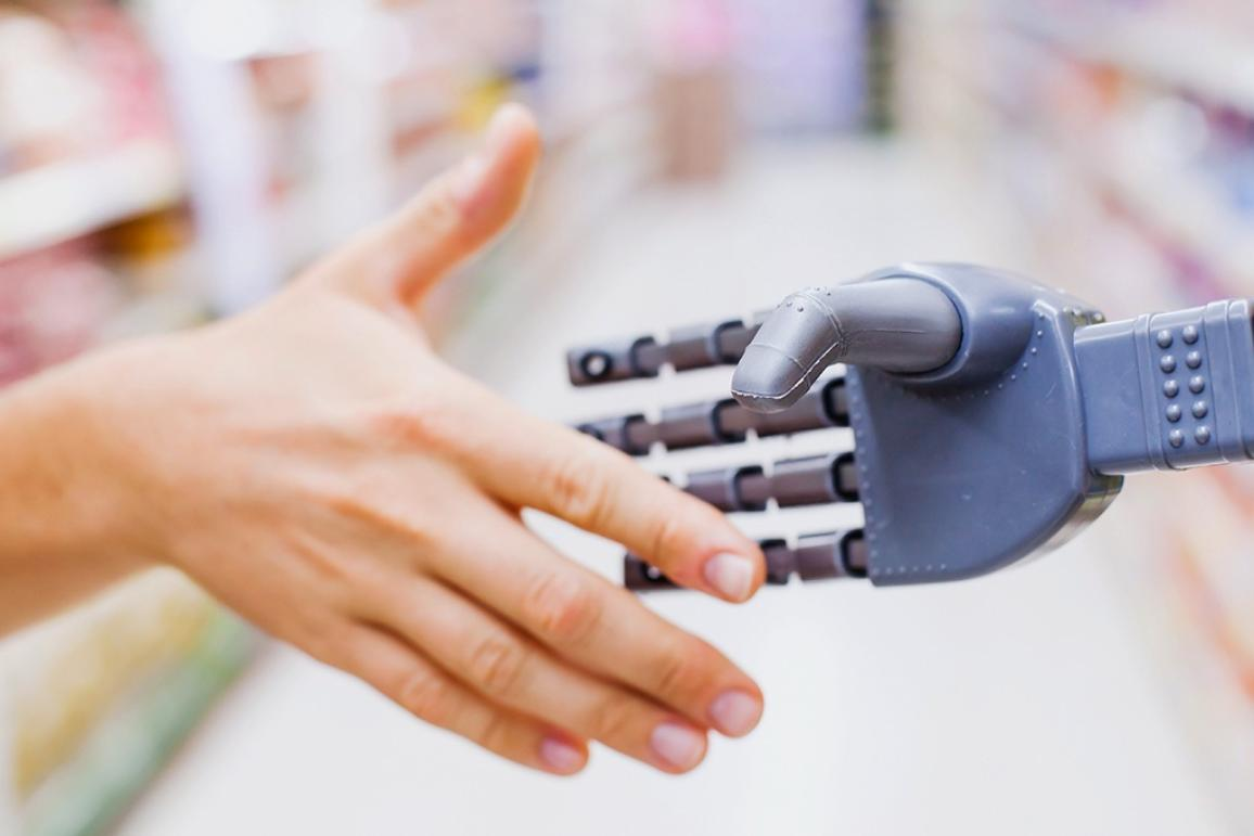 Robot and human hands in handshake