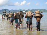 Rohingyas carrying supplies from boats to the lake shore
