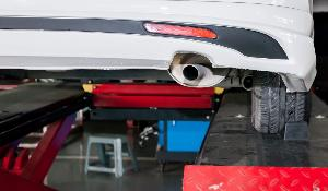 Car exhaust pipe in process of being modified in garage