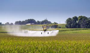 Duster plane on agricultural field