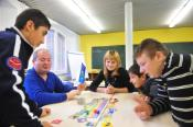 Refugee children with migration background playing in school with volunteers